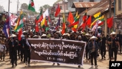 "Protesters holding a banner and flags take part in a demonstration against the military coup on ""Global Myanmar Spring Revolution Day"" in Kyaukme in Myanmar's Shan State, May 2, 2021. (Credit: Shwe Phee Myay News Agency)"