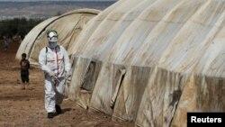 سول ڈیفنس کا ایک رکن ملک کے اندر بے گھر ہونے والے شامی باشندوں کے پناہ گزین کیمپ باب النور کو کرونا وائرس کے خطرے سے بچانے کے لیے جراثیم کش ادویات کا سپرے کر رہا ہے۔ 26 مارچ 2020