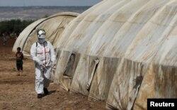 Anggota Pertahanan Sipil Suriah menyemprotkan cairan disinfektan di tenda di kamp Bab Al-Nour untuk mencegah penyebaran virus corona (COVID-19) di Azaz, Suriah, 26 Maret 2020. (Foto: Reuters)