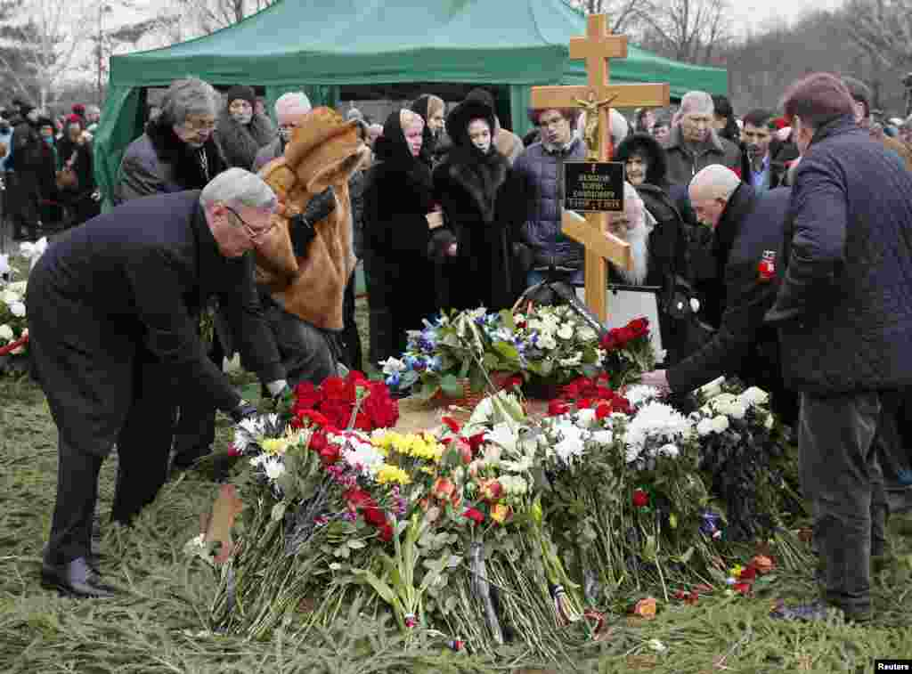 Mourners, including Mikhail Kasyanov (left), an opposition leader and former Russian prime minister, lay flowers at the grave of Russian leading opposition figure Boris Nemtsov during his funeral in Moscow, March 3, 2015.