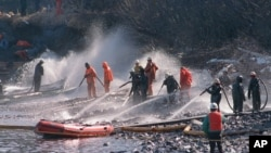 In this April 21, 1989 file photo, crews use high pressured hoses to clean up after the Exxon Valdez oil spill off the coast of Alaska. (AP Photo/Rob Stapleton, File)