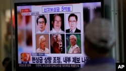 A man watches a TV news program on the reward poster of Yoo Byung-un at the Seoul Train Station in South Korea, May 26, 2014.