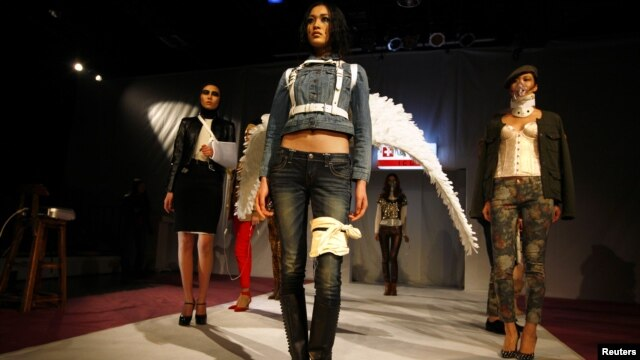Models pose on a makeshift catwalk during a fashion show organized by environmental group Greenpeace titled 'Toxic Threads - The Big Fashion Stitch-Up', in Beijing, November 20, 2012.