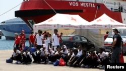 "Migrants sit on the ground after disembarking from Vos Hestia ship of NGO ""Save the Children"" in the Sicilian harbour of Augusta, Italy, Aug. 4, 2017."