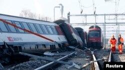 Dua orang anggota tim penyelamat berdiri di dekat kereta api pasca tabrakan di wilayah Rafz, sekitar 30 kilometer dari Zurich, Siwss (20/2).
