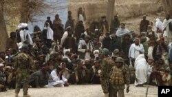 阿富汗國際部隊的士兵3月11日在坎大哈省本傑瓦爾區的美軍基地外守望聚集的阿富汗人