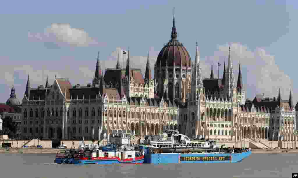 A barge carries the sightseeing boat, right, past the house of parliament on the Danube river after it was lifted from riverbed in Budapest, Hungary. Four people are still missing from the May 29 collision between the Hableany (Mermaid) sightseeing boat and the Viking Sigyn river cruise ship near to Budapest's Margit Bridge.