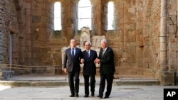 FILE - France's President Francois Hollande (l) and German President Joachim Gauck (r) walk with Robert Hebras, 88, one of the last survivors of the World War II massacre, as they visit the ruins of the church, in Oradour-sur-Glane, southwestern France, S