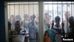 Palestinos esperan recibir alimentos en un centro de distribución de Naciones Unidas.