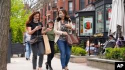 Sejumlah pejalan kaki berjalan di Newsbury Street, Boston, 2 Mei 2021. CDC mengatakan orang yang sudah vaksinasi COVID-19 dosis lengkap tak perlu pakai masker.