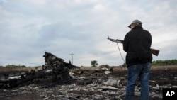 Pemberontak pro-Rusia menjaga lokasi jatuhnya pesawat Malaysia Airlines dekat desa Hrabove, Ukraina timur (19/7). (AP/Evgeniy Maloletka)