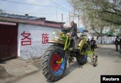 一位维吾尔人在新疆玛纳斯县驾驶自制的摩托车