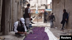 Free Syrian Army fighters prepare curtains to be erected as cover from snipers loyal to Syria's President Bashar al-Assad, Babeela area of suburban Damascus, March 30, 2013.