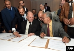 FILE - Awad Mohammed Abdul-Sadiq (L), the first deputy head of the Tripoli-based General National Congress (GNC), and Ibrahim Fethi Amish from the internationally recognised House of Representatives sign documents after reaching an agreement.
