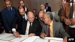 Awad Mohammed Abdul-Sadiq (L), the first deputy head of the Tripoli-based General National Congress (GNC), and Ibrahim Fethi Amish from the internationally recognized House of Representatives sign documents after reaching an agreement on ending the political deadlock in Libya following a meeting in the Tunisian town of Gammarth, on the outskirts of Tunis, Dec. 6, 2015.