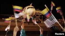 Niños ondean banderas de Colombia y Estados Unidos al partir un avión cargado con flores hacia los Estados Unidos, en el arranque del TLC entre estos dos países.