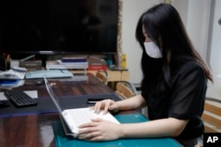 "Han Shin Bi, a high school senior in Seoul, demonstrates how to take online classes after an interview in Seoul, South Korea, on Sept. 18, 2020. ""Online classes were really inconvenient,"" said Han. Experts say the reduced interaction with teachers, digita"