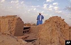 In this Friday, April 4, 2014, file photo, head mason Alassane Ramiya inspects the remains of tombs at a mausoleum after it was damaged in Timbuktu, Mali.