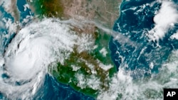 This satellite image provided by the National Oceanic and Atmospheric Administration shows Hurricane Olaf on the Pacific coast of Mexico approaching the Los Cabos resort region, early on Sept. 9, 2021.
