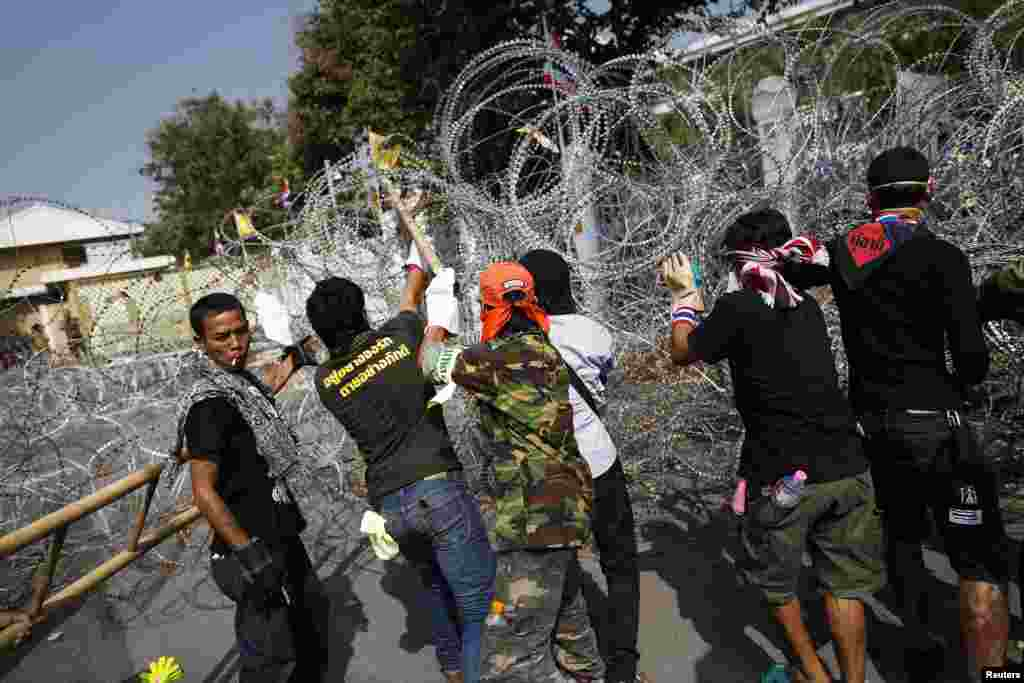 Anti-government protesters remove barbed wire after briefly entering the compound of the prime minister's office, known as the Government House, in Bangkok, Dec. 12, 2013.
