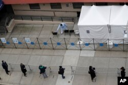 People stand in line as they wait to get tested for COVID-19 at a just opened testing center in the Harlem section of New York, Monday, April 20, 2020.
