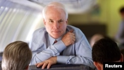 Arizona Senator and Republican presidential hopeful John McCain looks up while speaking with his campaign manager Rick Davis, left, and national political director John Weaver during a flight from South Carolina to California Feb. 4, 2000.