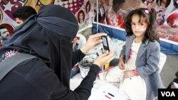 Nadia Abudllah mengambil foto seorang gadis cilik di tengah-tengah berlangsungnya protes anti-pemerintah di Sana'a (20/2).