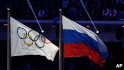 FILE - The Russian national flag (R) flies next to the Olympic flag during the closing ceremony of the 2014 Winter Olympics in Sochi, Russia, Feb. 23, 2014. A