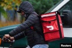 Seorang pengantar makanan Doordash mengendarai sepedanya di tengah hujan saat pandemi COVID-19 di wilayah Manhattan, New York City, New York, AS, 13 November 2020. (REUTERS/Carlo Allegri)