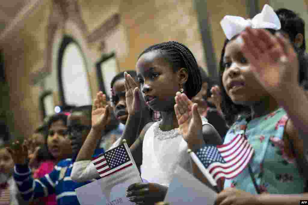 Children take the Oath of Allegiance as they become U.S. citizens during a citizenship ceremony at The Bronx Zoo, in The Bronx borough of New York City. Thirty-two children, ranging in age from 5 to 13 years old, attended the ceremony and became citizens.
