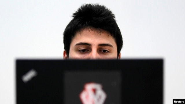 Romanian Razvan Cernaianu, formerly known as a hacker by the name of TinKode, works at his laptop, Bucharest, March 15, 2013.