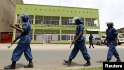 FILE - Riot police walk outside the Radio Publique Africaine broadcasting studio in Burundi's capital, Bujumbura, Apr. 26, 2015.