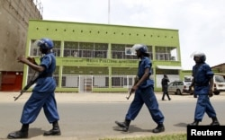 FILE - Riot policemen are seen walking outside the Radio Publique Africaine broadcasting studio in Burundi's capital, Bujumbura. Human Rights Watch is calling for a special envoy to Burundi and the exploring of a possible deployment of an international police force.