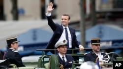 El nuevo presidente francés, Emmanuel Macron (centro) saluda a la multitud mientras se desplaza por la Avenida Champs-Eysees, en París, tras asumir la presidencia, el domingo 14 de mayo de 2017.