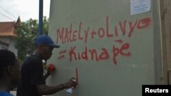 A demonstrator participating in an anti-government march sprays paints on a wall in Port-au-Prince