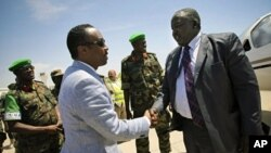 Uganda's Acting Foreign Affairs Minister Okello Oryem (R) is greeted by Somali Deputy Prime Minister and Minister for Defense Hussein Arab Issa upon his arrival at Mogadishu Airport, February 13, 2012