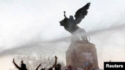 Los manifestantes sostienen una pancarta y banderas mapuche mientras se despliega el cañón de agua de la policía durante una protesta contra el modelo económico estatal de Chile en Santiago, Chile, 26 de octubre de 2019. REUTERS / Pablo Sanhueza