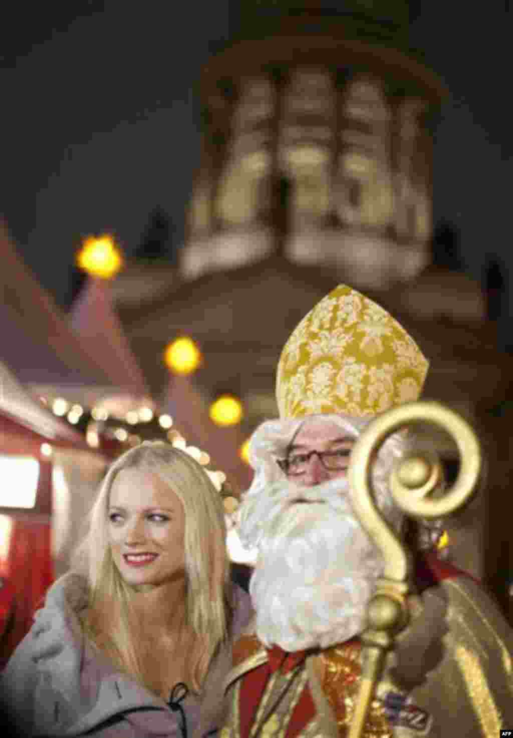 German model Franziska Knuppe, left, stands next to a man dressed as St Nicholas before the opining ceremony of the Christmas market on Gendarmenmarkt in Berlin on Monday, Nov. 22, 2010. Seen in the background is the French cathedral. (AP Photo/Gero Brelo