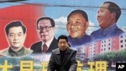 有人骑自行车路过山西的一块带有邓小平等领导人画像的公告牌(2009年2月)