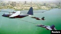 ເຮືອບິນທະຫານມາຣິນ ສະຫະລັດ KC-130 ຕື່ມນ້ຳມັນໃຫ້ເຮືອບິນລົບ F/A-18 ສອງລຳ.
