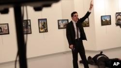 2016年12月19日,一个男子在土耳其首都安卡拉一个画廊,在一个倒地的人旁边做手势。