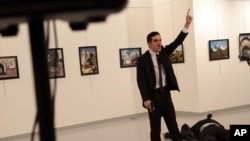 A man gestures near to the body of a man at a photo gallery in Ankara, Turkey, Monday, Dec. 19, 2016.