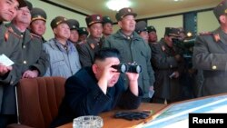 Picture released by North Korea's official KCNA news agency in Pyongyang Mar. 14, 2013 shows North Korean leader Kim Jong-un (C) and military officers watching a live shell firing drill to examine war fighting capabilities of artillery sub-units, whose mission is to strike DaeYeonpyeong island and Baengnyeong island of South Korea.