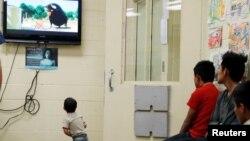 미국 애리조나주 투손에 위치한 미국관세국경보호청의 이민구치시설에서 구금돼 있는 어린아이가 TV 스크린으로 만화를 보고 있다.