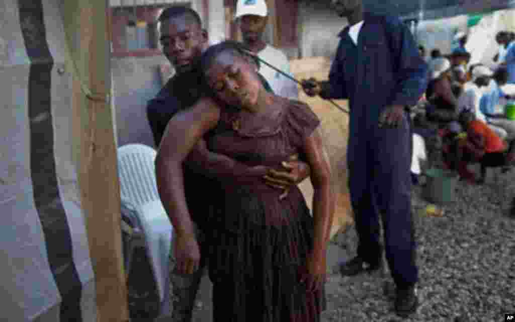 ARCHIV: A worker sprays with disinfectant a woman with symptoms of cholera as she is held by a relative at the entrance of St Catherine hospital in Cite Soleil in Port-au-Prince, Haiti, Wednesday, November 10, 2010 (Foto vom 10.11.10). Doctors and aid gro