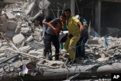 This photo provided by the Syrian anti-government activist group Aleppo Media Center (AMC), shows Syrians carrying a victim after barrel bombs were dropped on the Bab al-Nairab neighborhood in Aleppo, Syria, Aug. 27, 2016.