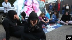 FILE - Families of Lebanese soldiers who were kidnapped by Islamic militants, block a main road during a protest after an al-Qaida-linked group in Syria says it has killed a kidnapped soldier Ali Bazzal, seen in poster with his daughter, in downtown Beirut, Lebanon on Dec. 6, 2014.