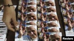 Una mujer ordena discos de música religiosa de Benedicto XVI. En el Líbano ha habido preparativos para la llegada del Papa.