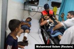 Seorang warga Palestina yang terluka terbaring di ranjang rumah sakit setelah mengikuti aksi protes di perbatasan Israel-Gaza di timur Kota Gaza, 21 Agustus 2021. (Foto: REUTERS/Mohammed Salem)