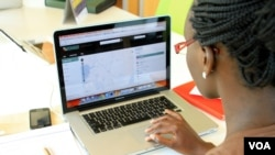 A woman looks at the Uchaguzi Web site at the iHub, Nairobi, Kenya, Feb. 28, 2013. (J. Craig/VOA)